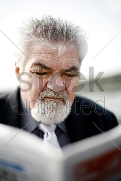 senior businessman reading newspaper stock photo