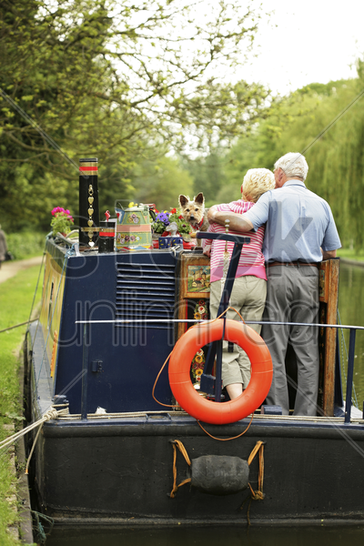 senior couple and their dog on the houseboat stock photo