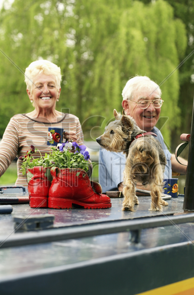 senior couple and their pet dog on the houseboat stock photo