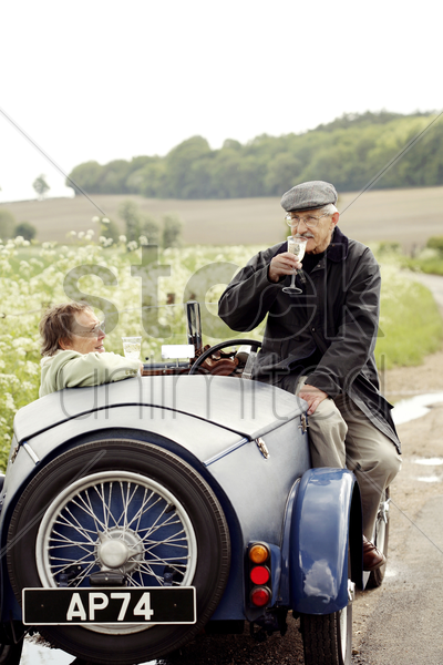 senior couple drinking wine in the car stock photo