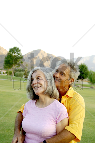 senior couple embracing in the park stock photo