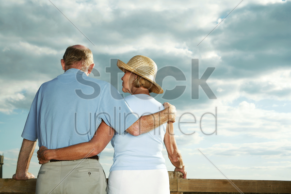 senior couple enjoying beautiful field scenery stock photo