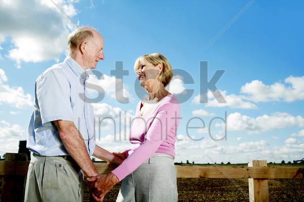senior couple holding hands while looking at each other stock photo