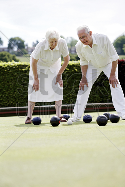 senior couple lawn bowling in the bowling green stock photo