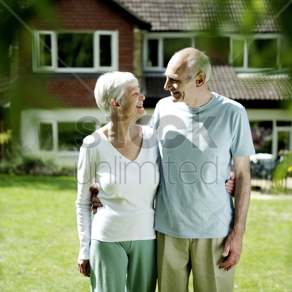senior couple standing in front of their house stock photo