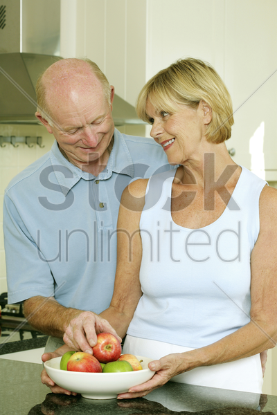 senior couple with a bowl of fruits stock photo