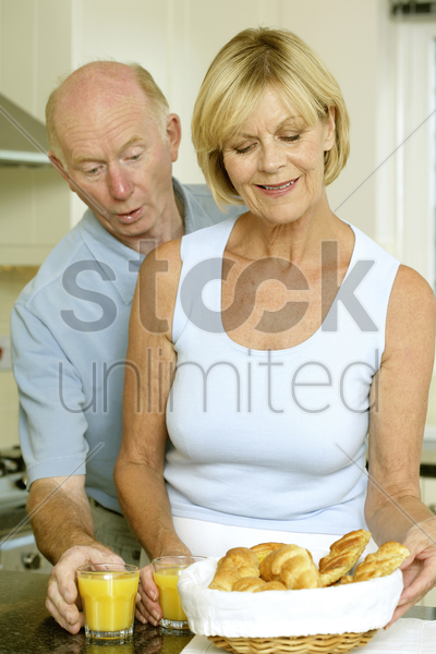 senior couple with orange juice and freshly baked croissants stock photo