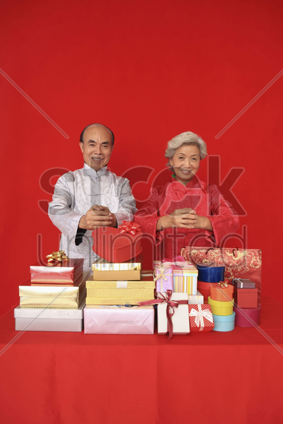 senior man and senior woman greeting happy chinese new year with gift boxes and paper bags in front of them stock photo