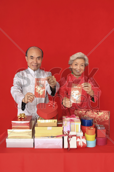 senior man and senior woman holding red packets and smiling stock photo