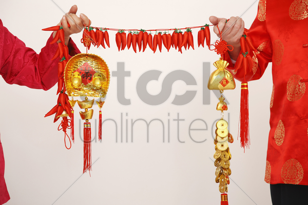 senior man and woman holding chinese decorations stock photo