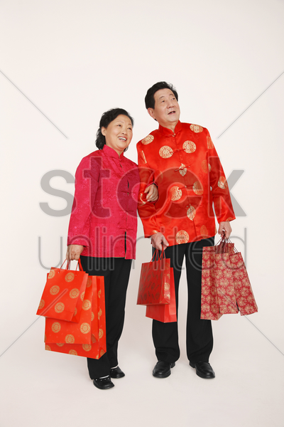 senior man and woman holding shopping bags stock photo