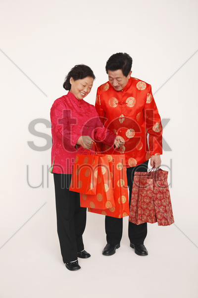 senior man and woman looking into shopping bag stock photo
