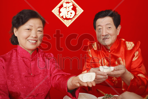 senior man and woman making chinese dumplings stock photo