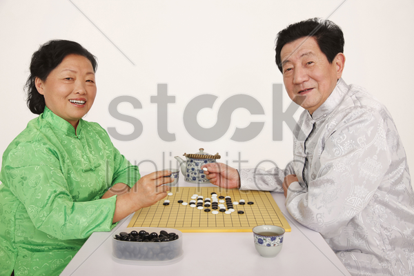 senior man and woman playing japanese board game stock photo