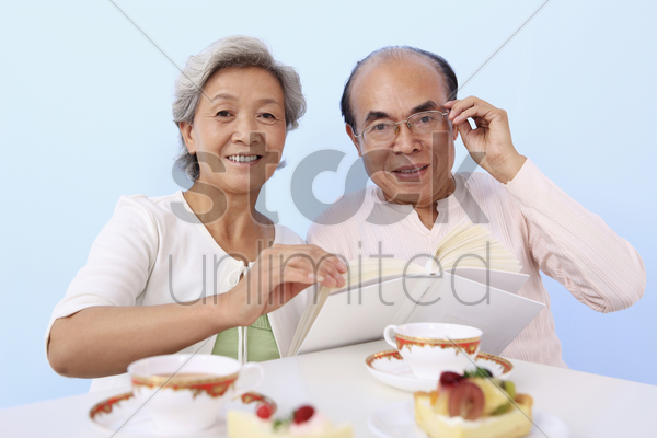 senior man and woman reading book while enjoying cake and tea stock photo