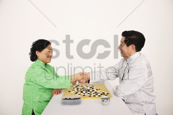 senior man and woman shaking hands stock photo