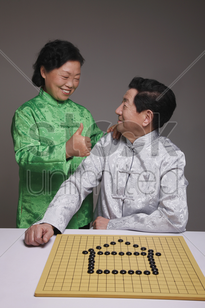 senior man arranging black pebbles into a house, senior woman showing him thumbs up stock photo