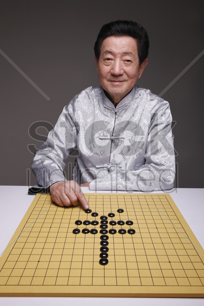 senior man arranging black pebbles into yen symbol stock photo