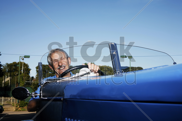 senior man driving in the car stock photo