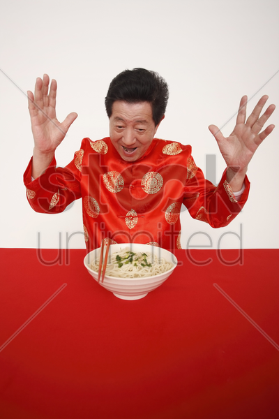 senior man excited looking at a bowl of noodles stock photo