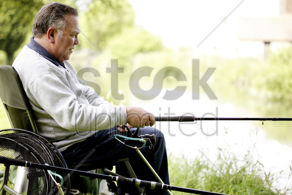senior man fishing by the river stock photo