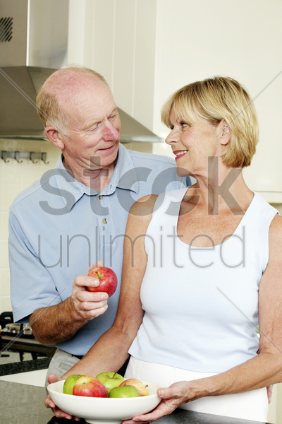 senior man getting an apple from his wife stock photo