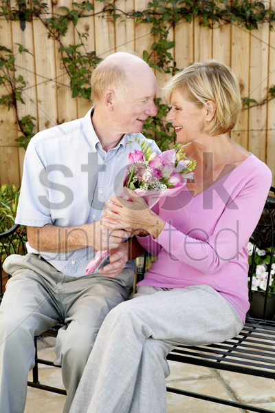 senior man giving his wife a bouquet of flowers stock photo