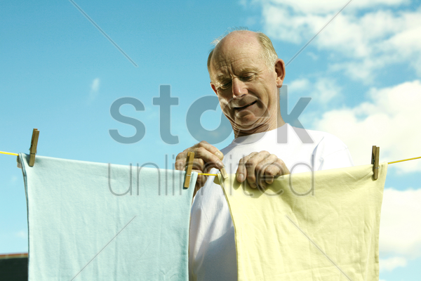 senior man hanging laundry on washing line stock photo