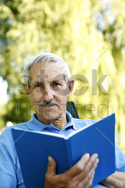 senior man holding a book while looking at the camera stock photo