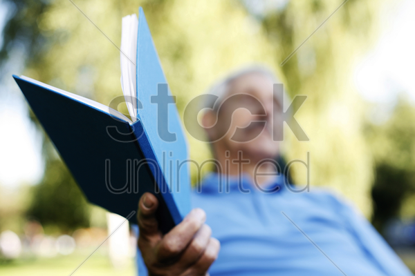 senior man holding a book stock photo