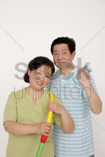 senior man holding dumbbell while senior woman is holding hula hoop stock photo