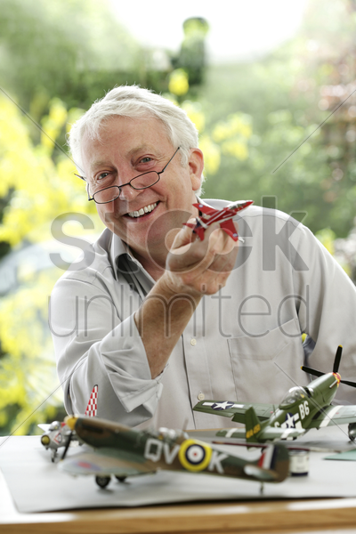 senior man holding model airplane stock photo