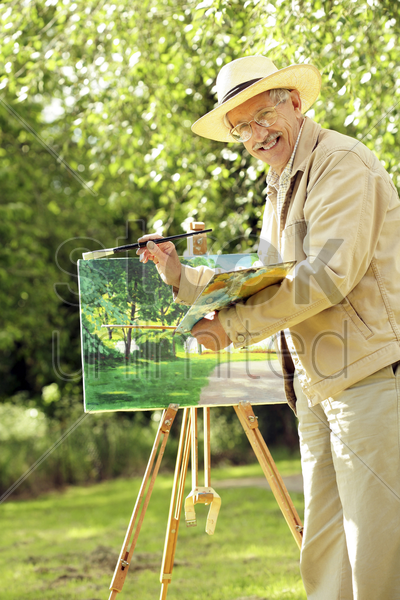 senior man holding paintbrush and a palette stock photo