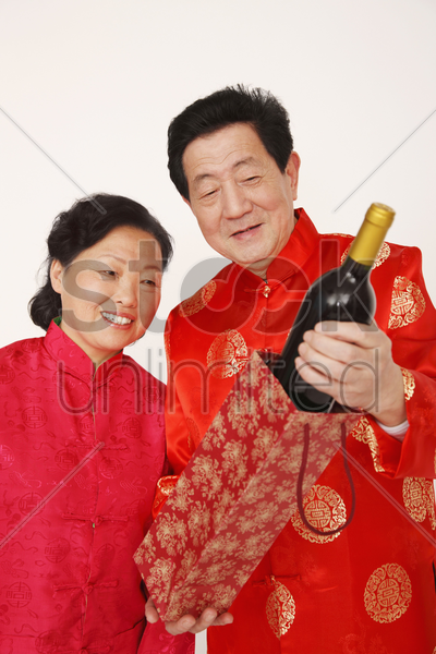 senior man is showing senior woman a bottle of wine stock photo
