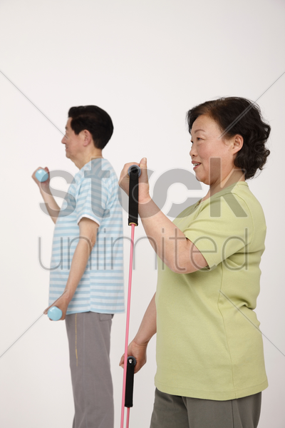 senior man lifting weight while senior woman is exercising with elastic band stock photo
