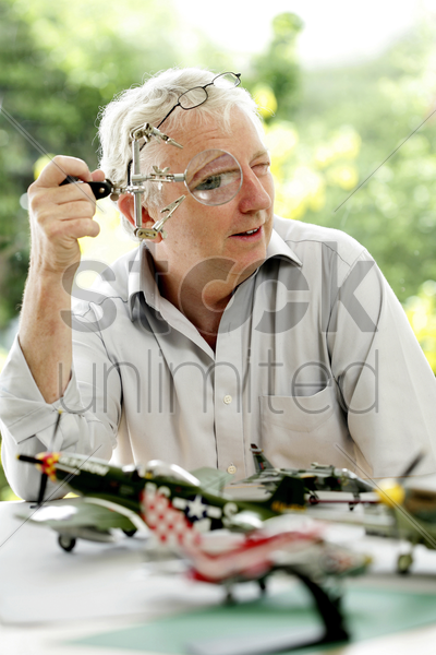 senior man looking through a magnifying glass stock photo
