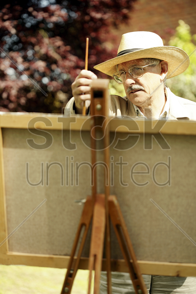 senior man measuring with a paintbrush while drawing stock photo