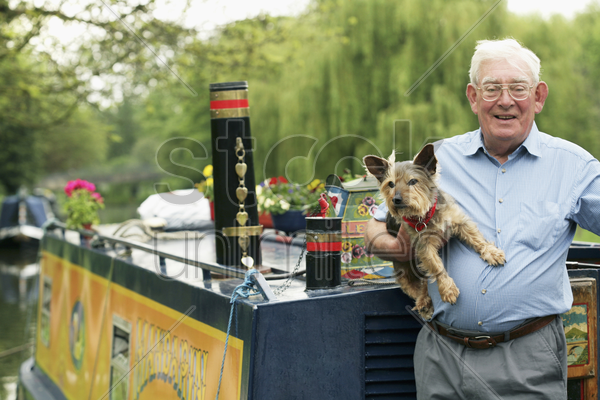 senior man posing with his dog on houseboat stock photo