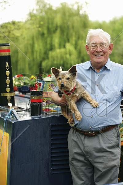 senior man posing with his dog on the houseboat stock photo