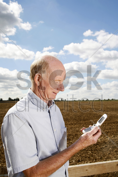 senior man reading a message on his mobile phone stock photo