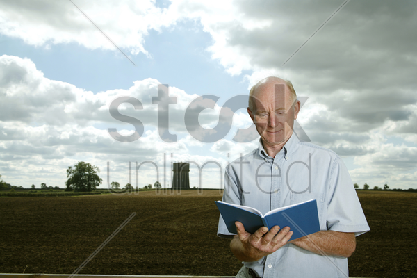 senior man reading book in the park stock photo