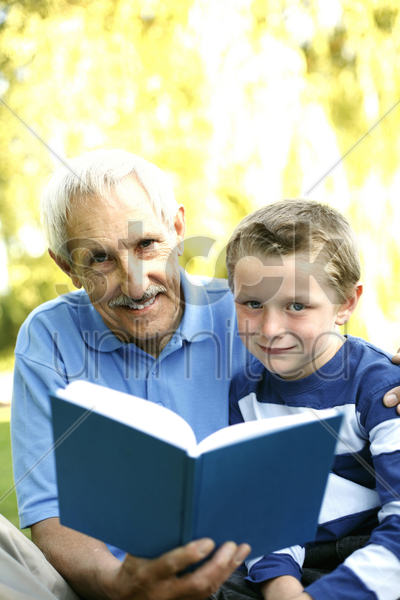 senior man reading for his grandson stock photo