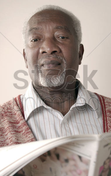 senior man reading newspaper stock photo