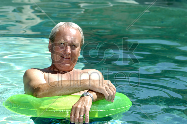 senior man relaxing in the pool stock photo