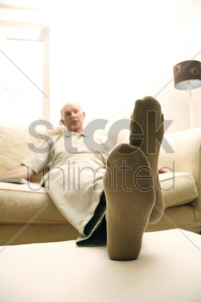 senior man resting on couch stock photo