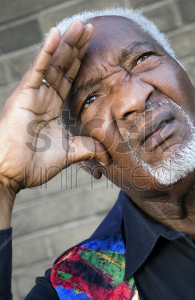 senior man shielding his eyes with his hand stock photo