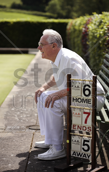 senior man sitting on a bench in a bowling green stock photo