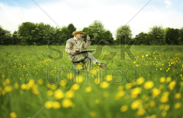 senior man sitting on a chair drawing stock photo