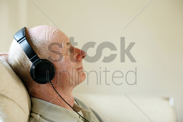 senior man sitting on the couch listening to music on the headphones stock photo