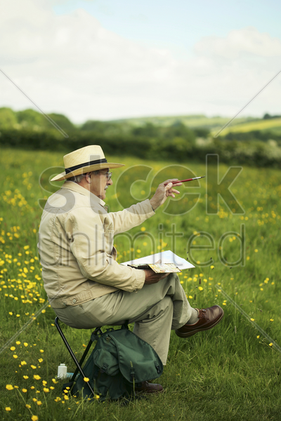 senior man sitting on the field drawing stock photo